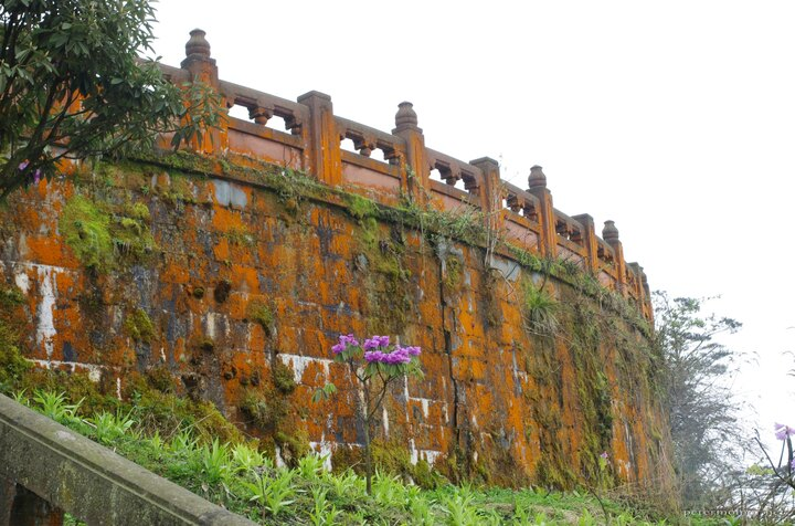 The outer wall of the monastery, covered in various lichens and fungi